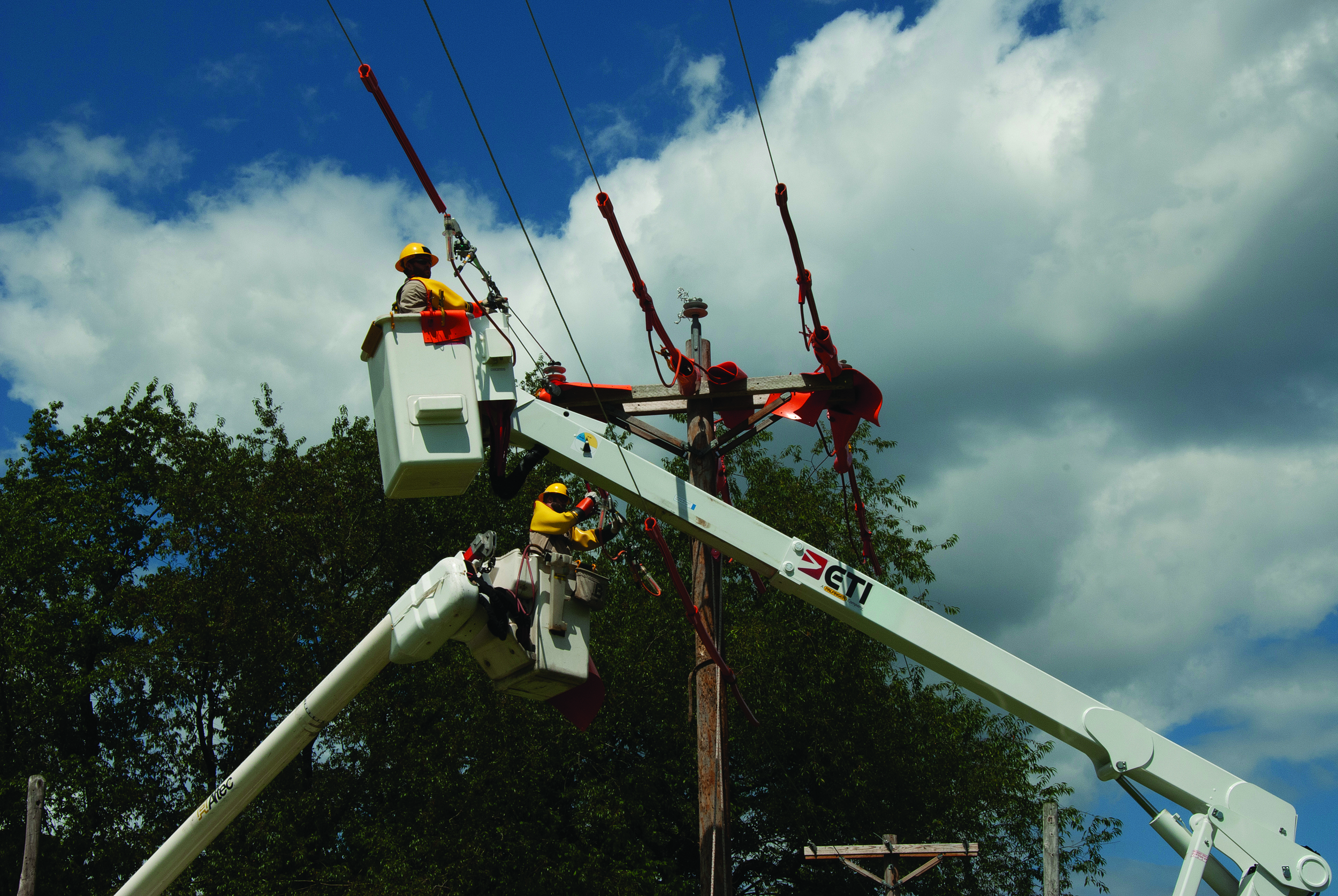 HANDLE WITH CARE: Lineworkers cover power lines with rubber mats to avoid electrical contact before practicing equipment change-outs during a JT&S Advanced Rubber Glove School at REA Energy Cooperative in Indiana, Pa.