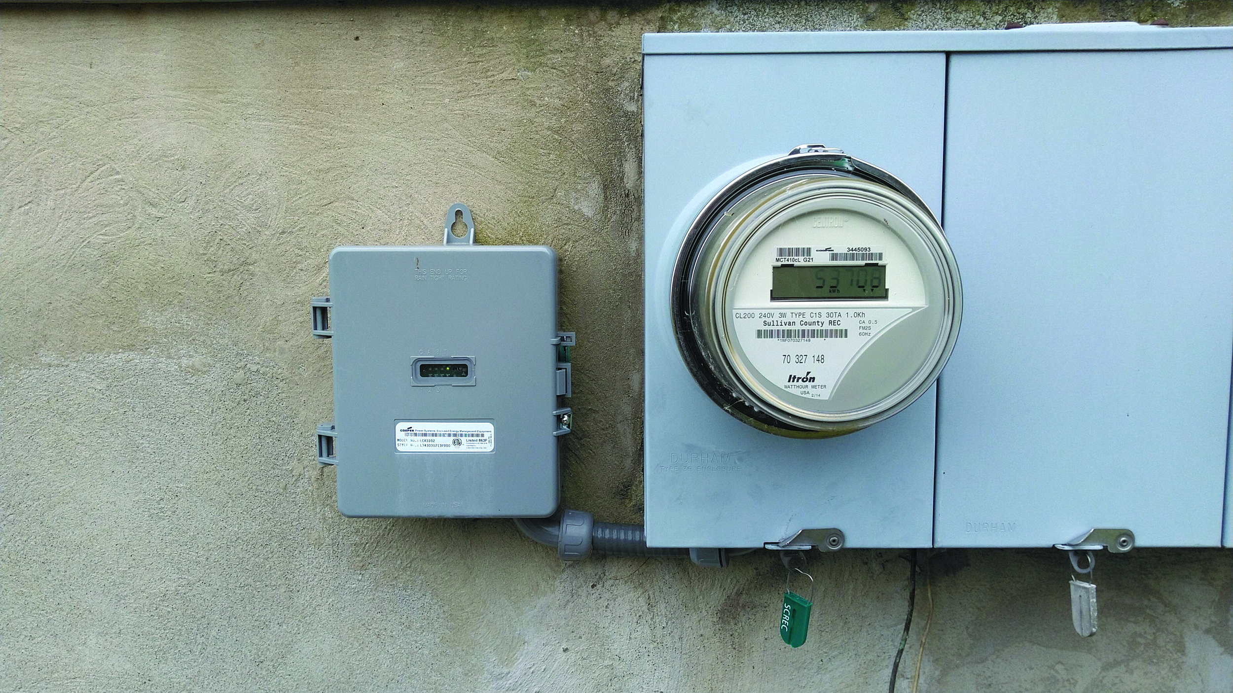 An electric meter attached to the home of a Sullivan County REC member monitors energy use of an electric thermal storage system.
