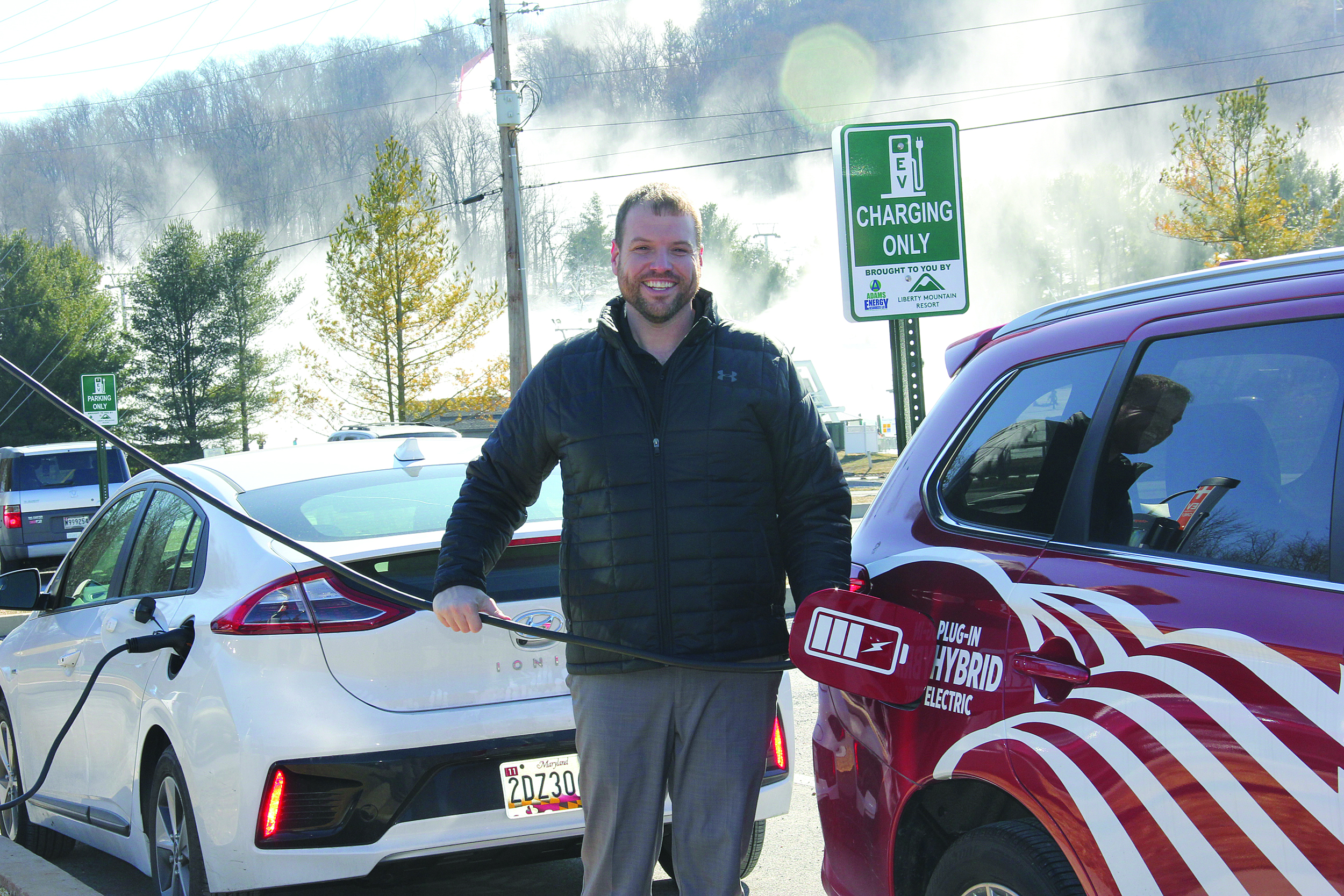 Mike Johnson, key accounts/senior safety specialist at Adams EC, plugs in a hybrid electric vehicle to a charging station operated by the cooperative's subsidiary, Adams Energy Resources, LLC.
